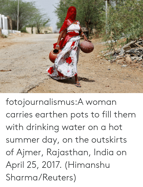 Reuters: fotojournalismus:A woman carries earthen pots to fill them with drinking water on a hot summer day, on the outskirts of Ajmer, Rajasthan, India on April 25, 2017. (Himanshu Sharma/Reuters)